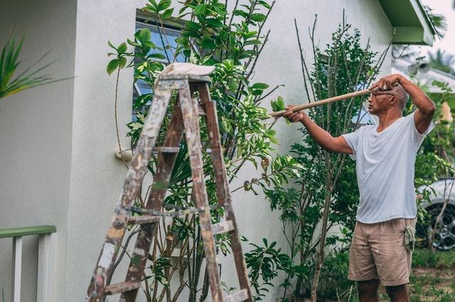 Un homme peignant une maison