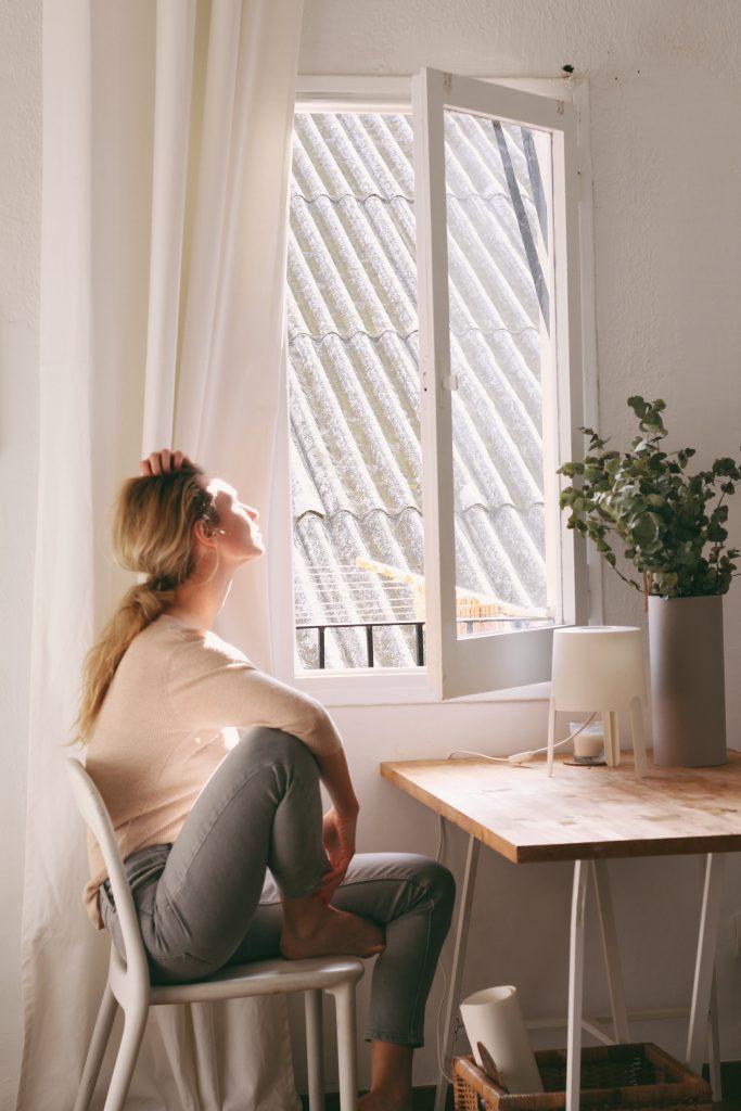 Une femme assise sur une chaise à coté d'une fenêtre.