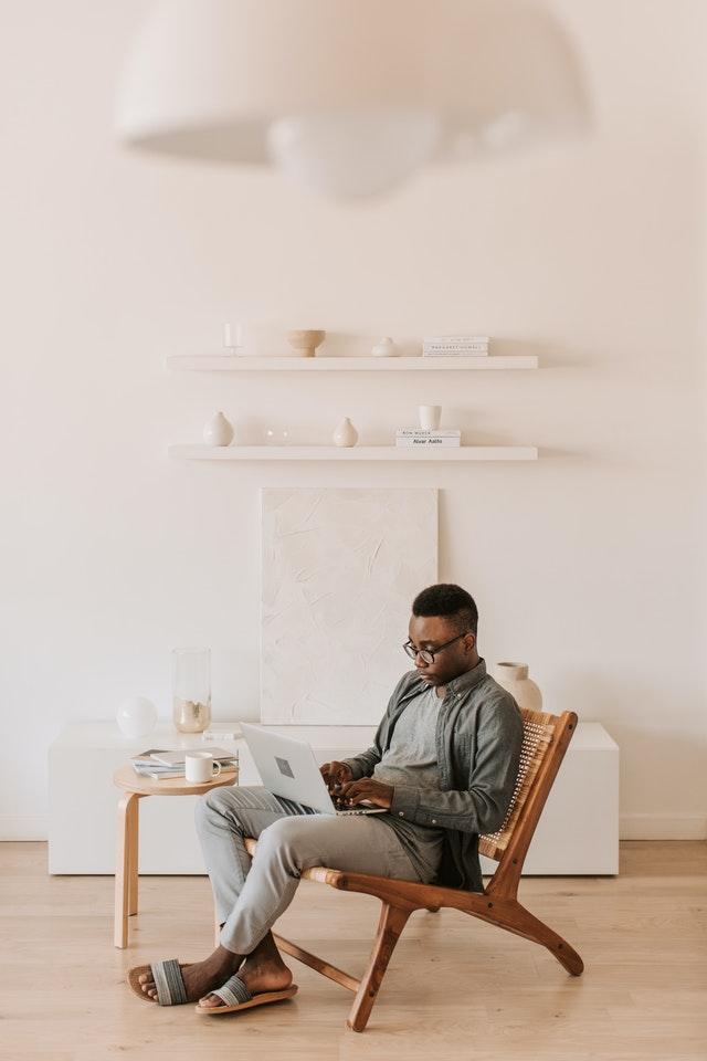 Un homme assis sur une chaise et tenant son ordinateur portable.